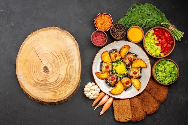 Vista de cima deliciosos pãezinhos de berinjela, prato cozido com batatas e pães no fundo escuro, cozinhando pratos fritos assar batata