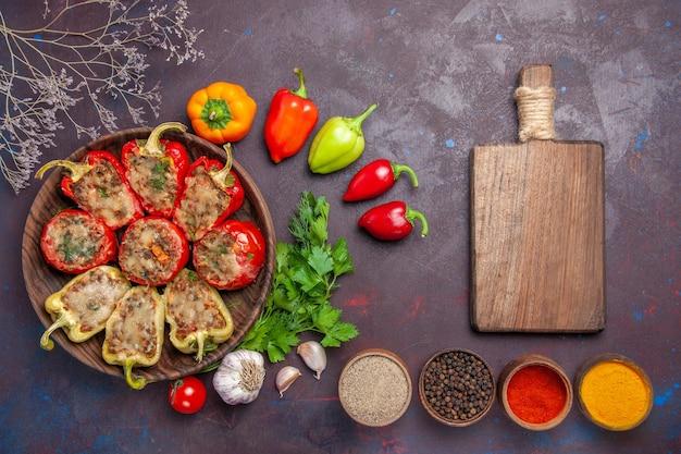Vista de cima deliciosos pimentões assados no prato com recheio de carne moída e vegetais na mesa escura.
