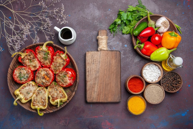 Vista de cima deliciosos pimentões cozidos no prato com recheio picado e temperos no fundo escuro