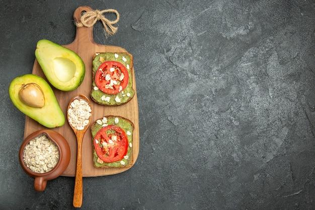 Vista de cima deliciosos sanduíches com abacate e tomate vermelho no fundo cinza.