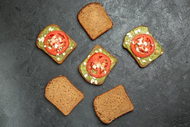 Vista de cima deliciosos sanduíches com wassabi e tomate vermelho no fundo cinza.