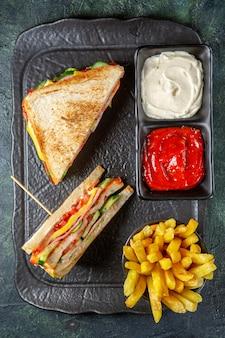 Vista de cima deliciosos sanduíches de presunto com batata frita e temperos na superfície escura