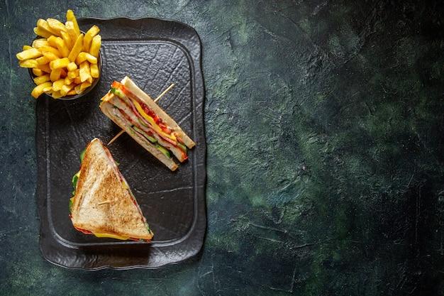 Vista de cima deliciosos sanduíches de presunto com batata frita na superfície escura