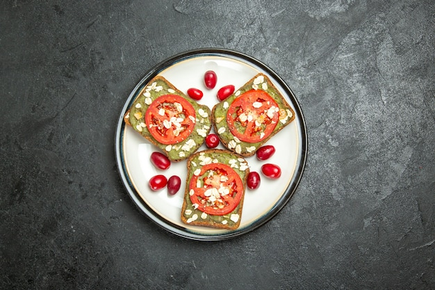 Vista de cima deliciosos sanduíches úteis com macarrão de abacate e tomate dentro do prato em um fundo cinza sanduíche de hambúrguer com pão e pão