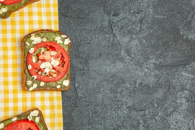 Vista de cima deliciosos sanduíches úteis com macarrão de abacate e tomate no fundo cinza sanduíche de hambúrguer com pão e pão de lanche