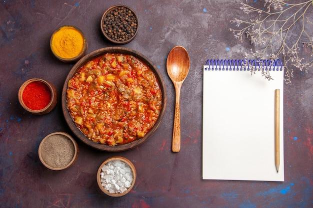 Vista de cima deliciosos vegetais cozidos com diferentes temperos em uma mesa escura, molho de sopa, comida vegetal