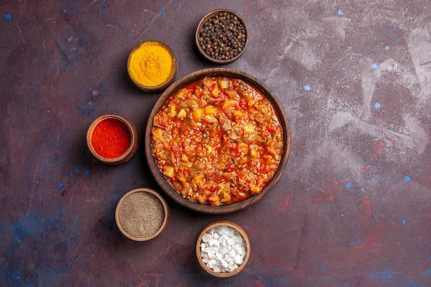 Vista de cima deliciosos vegetais cozidos com diferentes temperos no fundo escuro refeição de molho de sopa comida de vegetais
