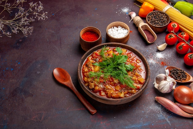 Vista de cima deliciosos vegetais cozidos fatiados com verduras e temperos em uma mesa escura, sopa, molho alimentar