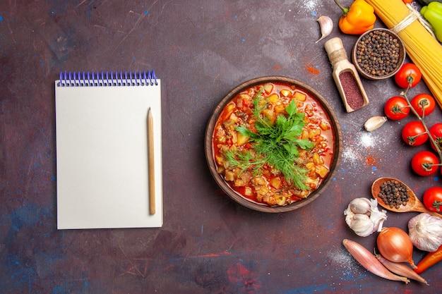 Vista de cima deliciosos vegetais cozidos fatiados com verduras e temperos no fundo escuro com molho de sopa de comida