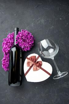 Vista de cima dia dos namorados presente com flores e garrafa de vinho no fundo escuro sentimentos de amor casal presente cor álcool casamento