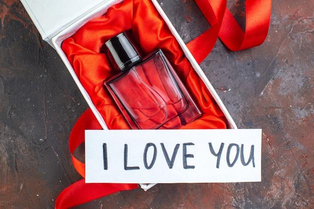 Vista de cima dia dos namorados presente fragrância na superfície escura presente perfume amor sentimento cor felicidade mulher