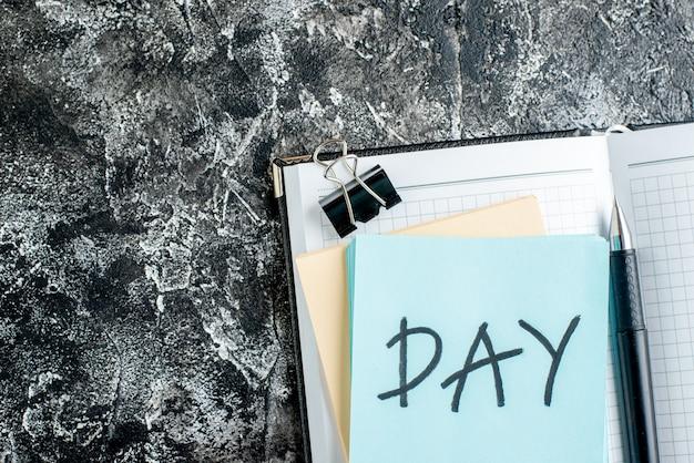 Vista de cima dia nota escrita dentro do bloco de notas aberto em fundo cinza