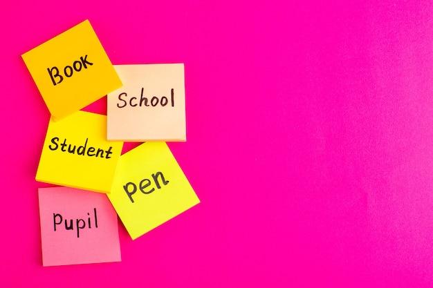 Vista de cima diferentes adesivos com palavras em toda a superfície rosa