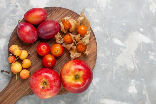 Vista de cima diferentes ameixas formadas frutas ácidas e frescas com cerejas na mesa branca clara.