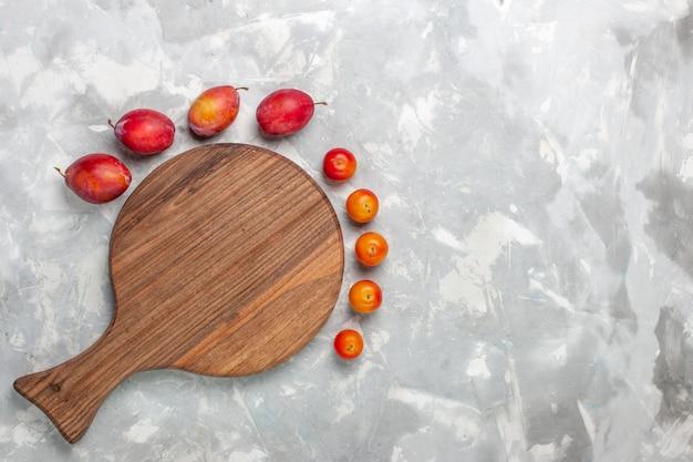 Vista de cima diferentes ameixas formadas frutas ácidas e frescas sobre a mesa branca.
