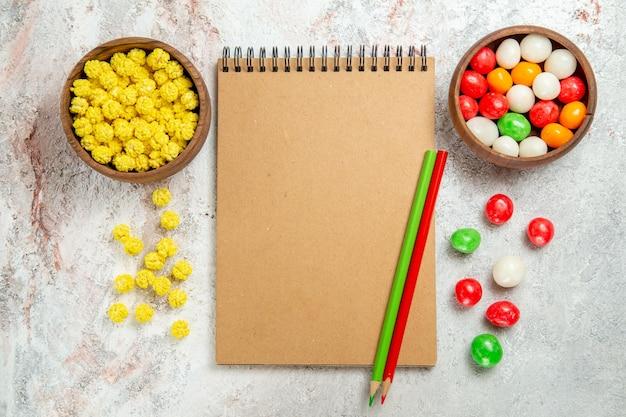 Vista de cima diferentes balas coloridas na cor de mesa branca açúcar doce
