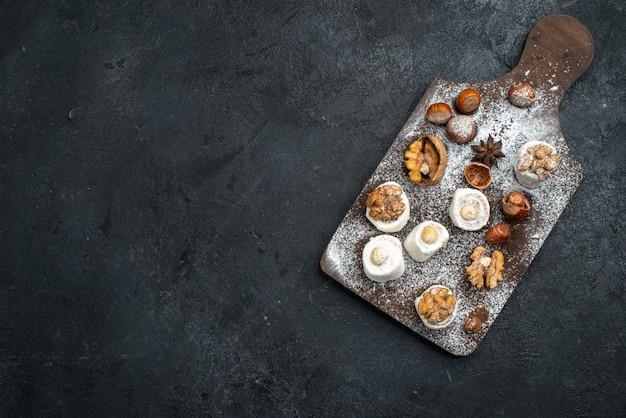 Vista de cima diferentes biscoitos com bolos e nozes na superfície cinza escura