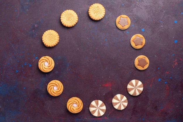 Vista de cima diferentes biscoitos com creme dentro em uma superfície escura