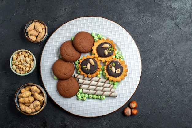 Vista de cima diferentes biscoitos de chocolate com nozes em uma superfície cinza-escuro biscoito de açúcar e bolo doce
