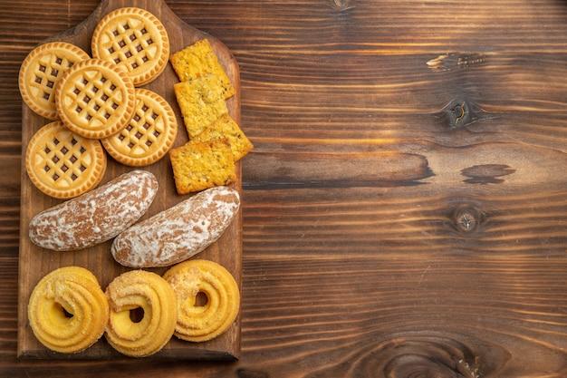 Vista de cima diferentes biscoitos doces para chá na mesa de madeira marrom