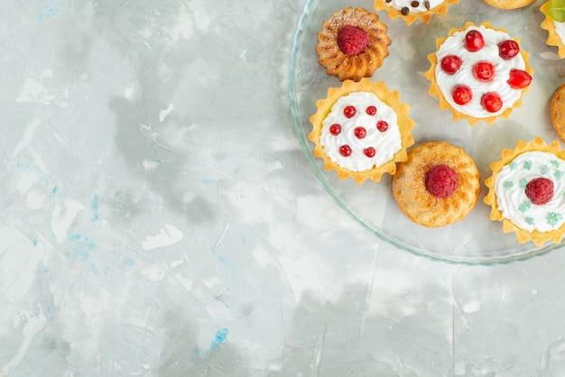 Vista de cima diferentes bolos com creme e frutas frescas na superfície clara biscoito açúcar doce