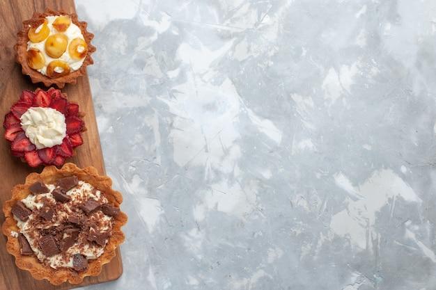 Vista de cima diferentes bolos cremosos com chocolate e frutas no bolo de mesa branco assar biscoito doce açúcar fruta