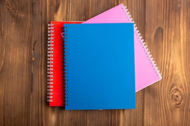 Vista de cima diferentes cadernos coloridos sobre a mesa marrom
