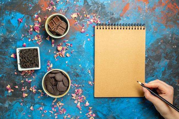 Vista de cima diferentes chocolates em pequenas tigelas, lápis de caderno na mão da mulher na superfície azul vermelha