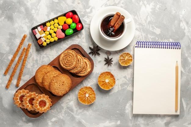 Vista de cima diferentes cookies com doces e uma xícara de chá no fundo branco