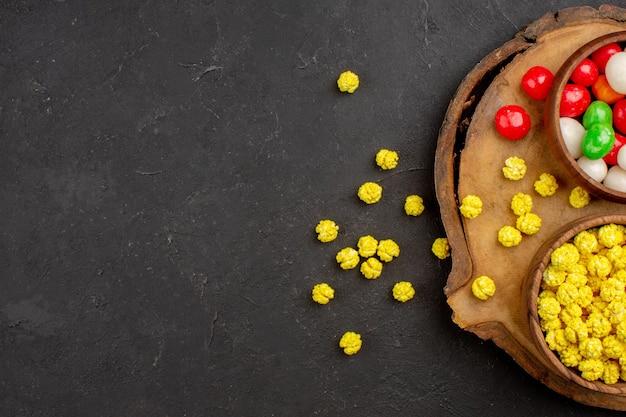 Vista de cima diferentes doces coloridos na mesa escura.