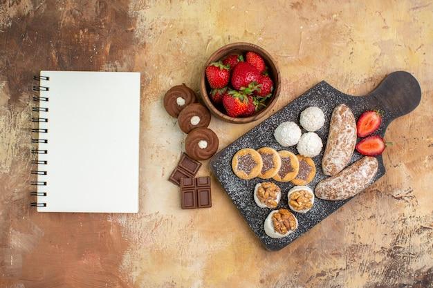 Vista de cima diferentes doces com biscoitos e frutas na mesa de luz