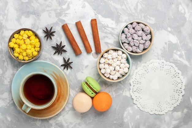 Vista de cima diferentes doces com macarons franceses e uma xícara de chá no fundo branco doce açúcar doce assar bolo biscoito de torta de chá