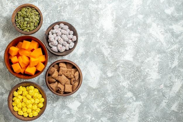 Vista de cima diferentes doces com sementes na superfície branca do chá de doces da cor da flor