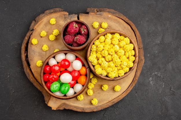 Vista de cima diferentes doces, doces coloridos em uma mesa escura.