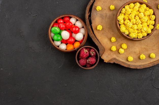 Vista de cima diferentes doces, doces coloridos na mesa escura.