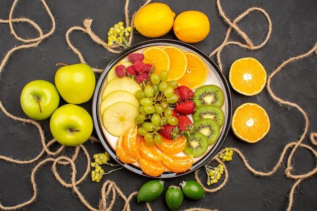Vista de cima diferentes fatias de frutas frescas dentro do prato em fundo escuro dieta frutas frescas maduras