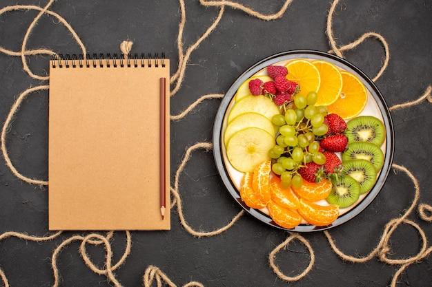 Vista de cima diferentes frutas fatiadas dentro do prato em fundo escuro dieta frutas frescas maduras Foto gratuita