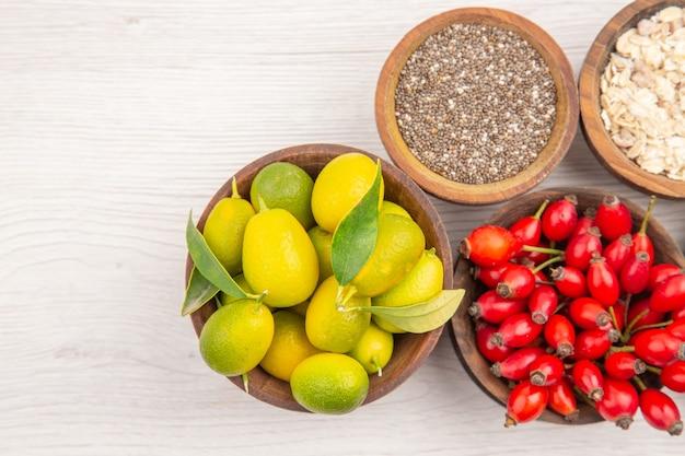Vista de cima diferentes frutas frescas dentro de pratos em fundo branco dieta madura exótica vida saudável cor tropical