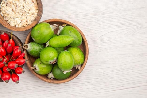 Vista de cima diferentes frutas frescas dentro de pratos em fundo branco dieta madura vida saudável cor tropical