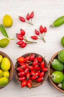 Vista de cima diferentes frutas frescas dentro de pratos em fundo branco exótica cor madura vida saudável tropical