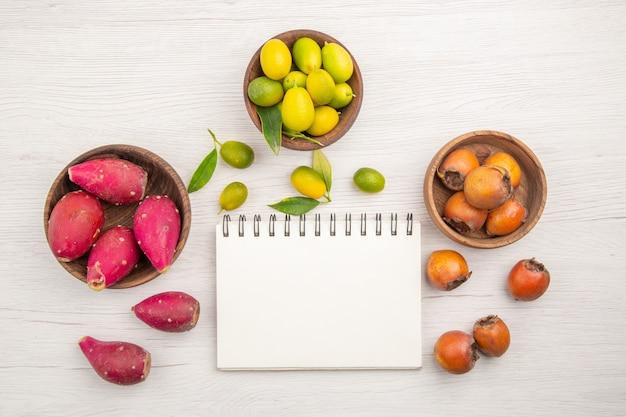 Vista de cima diferentes frutas frescas dentro de pratos em fundo branco frutas dieta madura tropical cor exótica vida saudável