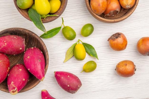 Vista de cima diferentes frutas frescas dentro de pratos em fundo branco frutas dieta tropical madura cor exótica