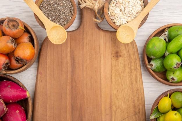 Vista de cima diferentes frutas frescas dentro de pratos em fundo branco maduro vida saudável cor dieta exótica