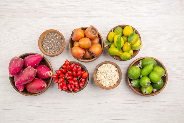 Vista de cima diferentes frutas frescas dentro de pratos em fundo branco maduro vida saudável cor tropical dieta