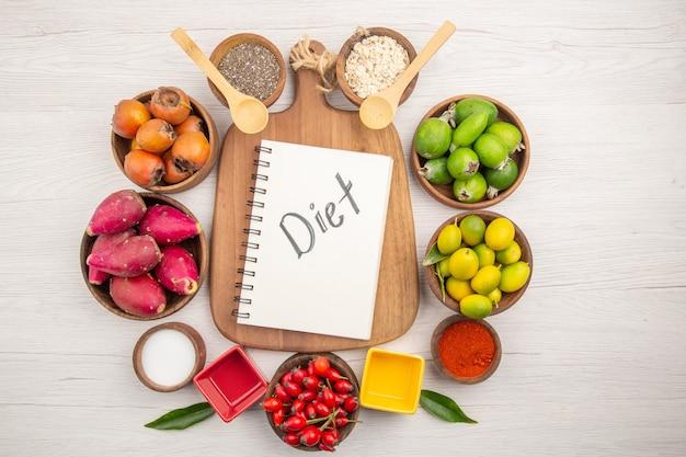 Vista de cima diferentes frutas frescas dentro de pratos em fundo branco tropical cor madura dieta exótica vida saudável
