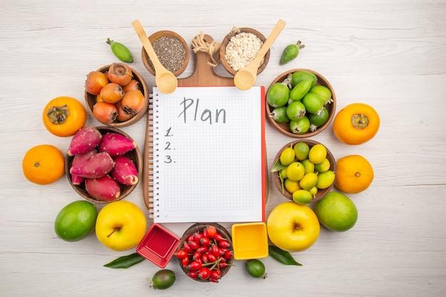 Vista de cima diferentes frutas frescas dentro de pratos em fundo branco tropical cor madura dieta suave exótica saúde