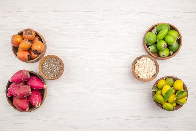 Vista de cima diferentes frutas frescas dentro de pratos em fundo branco tropical maduro exótico vida saudável cor dieta