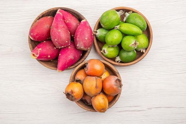 Vista de cima diferentes frutas frescas dentro de pratos na mesa branca fruta tropical madura dieta exótica cor vida saudável