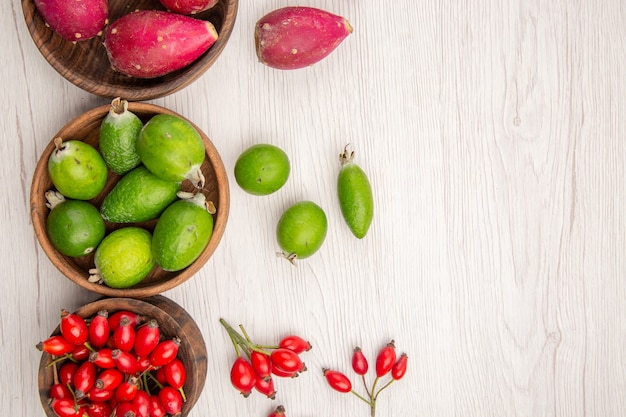 Vista de cima diferentes frutas frescas dentro de pratos no fundo branco dieta madura exótica cor vida saudável tropical