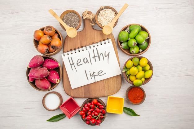 Vista de cima diferentes frutas frescas dentro de pratos no fundo branco dieta madura tropical exótica vida saudável